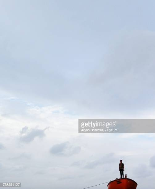 Man Standing On Boat Against Cloudy Sky