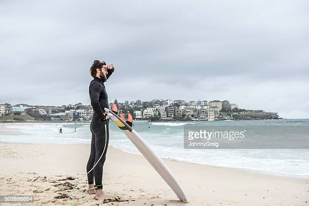 Man standing on Bondi Beach with surfboard looking at sea
