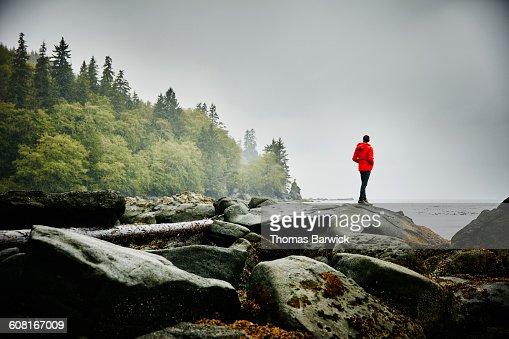 Man standing on boulders on shoreline of ocean