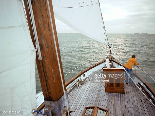 Man standing on bow of sailboat, overlooking sea, elevated view