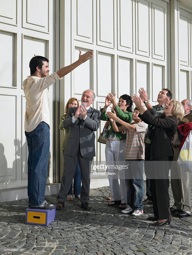 Man standing on box in street holding out arms to applauding crowd