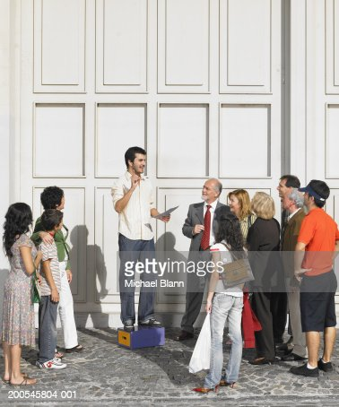 Man standing on box in street speaking to crowd