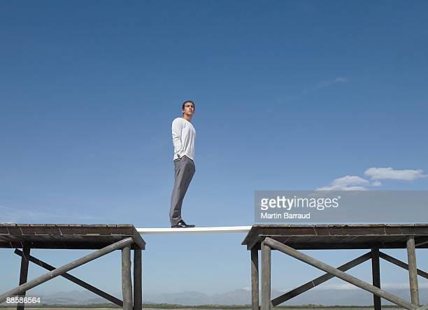 Man standing on bridge over gap