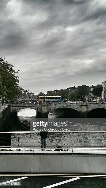 Man Standing On Bridge Over River By City Against Cloudy Sky