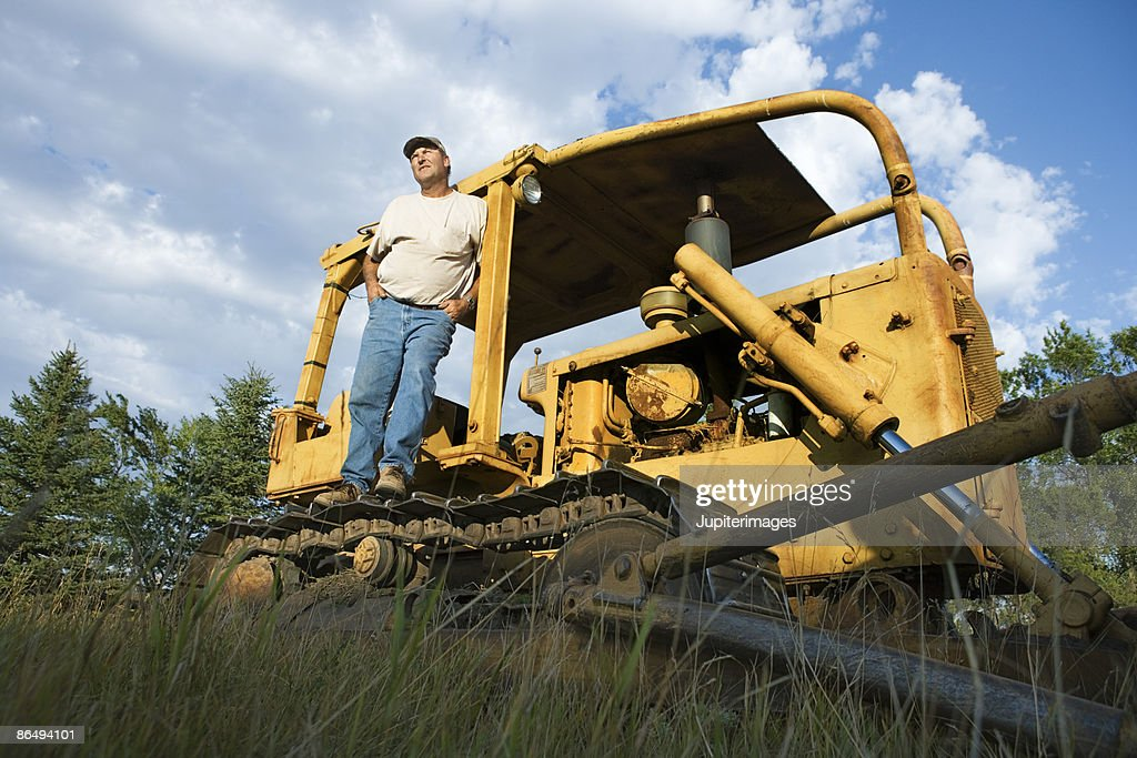 Man On Bulldozer : Man standing on bulldozer stock photo getty images