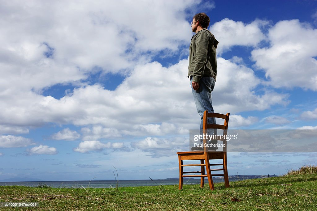 Man standing on chair in field, looking at landscape, side view : Photo