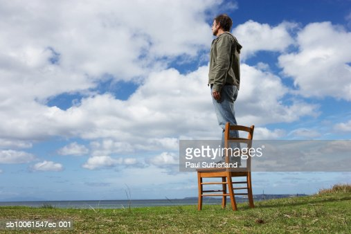 Man standing on chair in field, looking at landscape, side view : Stock Photo