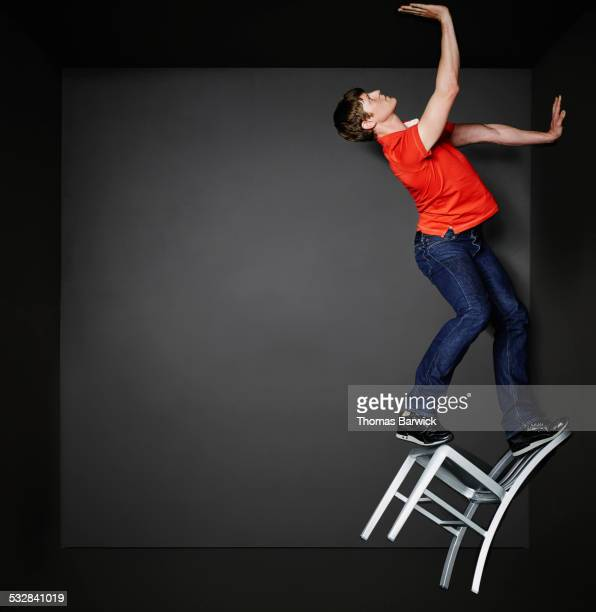Man standing on chair reaching for ceiling