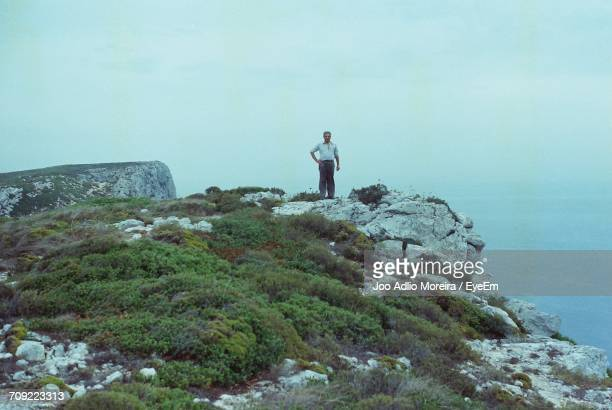 Man Standing On Cliff Against Sea