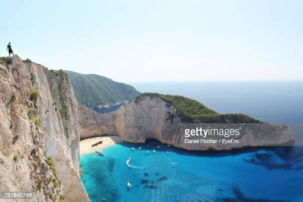 Man Standing On Cliff Against Sky At Navagio