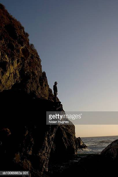 Man standing on cliff by the ocean