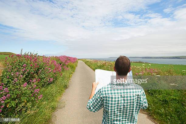 Man standing on country lane with road map