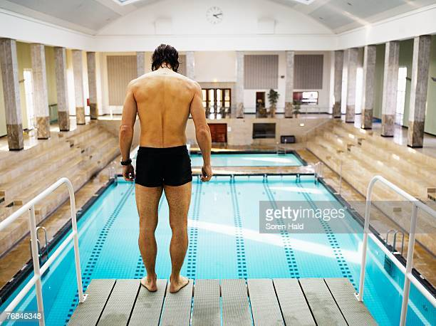 Man standing on diving board, rear view