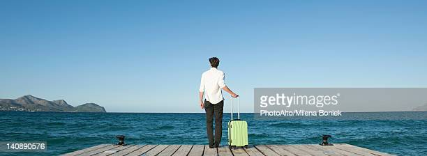 Man standing on dock with suitcase, looking at ocean view, rear view