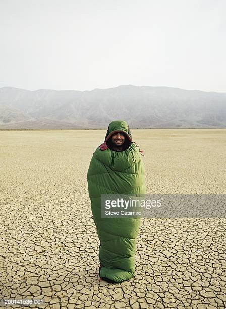 Man standing on dry lake wrapped in sleeping bag