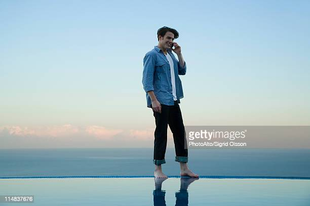 Man standing on edge of infinity pool, talking on cell phone