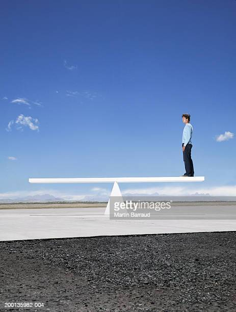 Man standing on end of see saw outdoors, side view