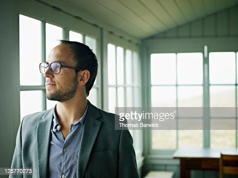Man standing on front porch of vacation home : Stock Photo