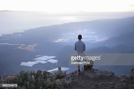 Man standing on high rock looking at city