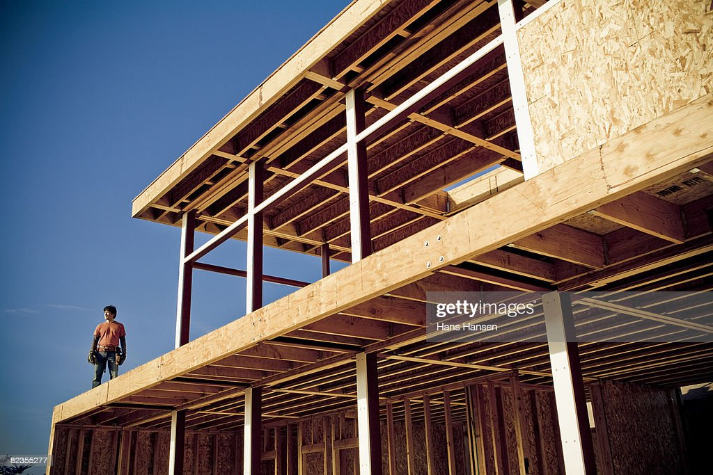 Man standing on house under construction : Stock Photo