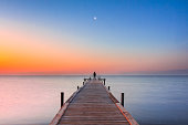 A man standing at the end of a jetty watching the moon in the sky, at sunrise sunset time. Silhouette man. Beach landscape