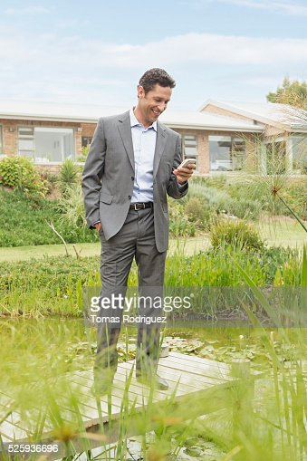 Man standing on jetty by pond in back yard and text messaging : Stock Photo