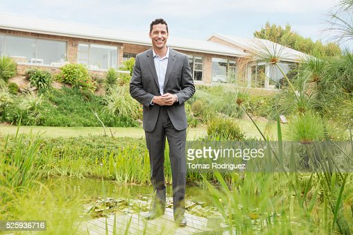 Man standing on jetty by pond in back yard : Stock Photo
