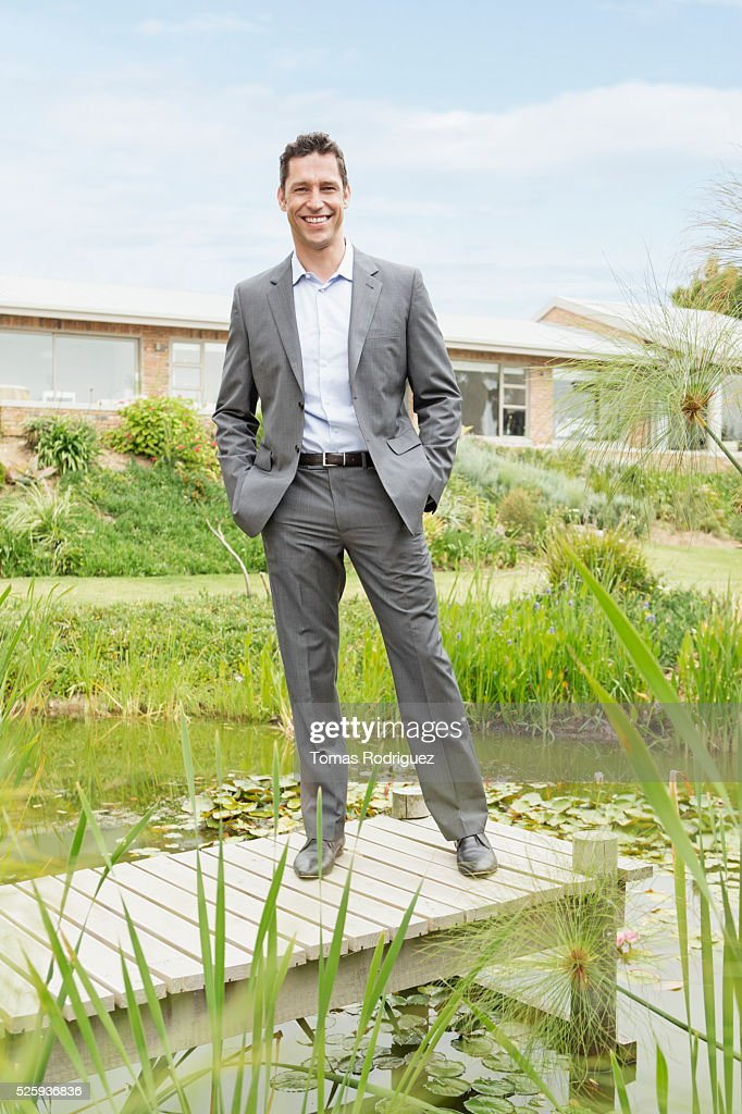 Man standing on jetty by pond in back yard : Foto de stock