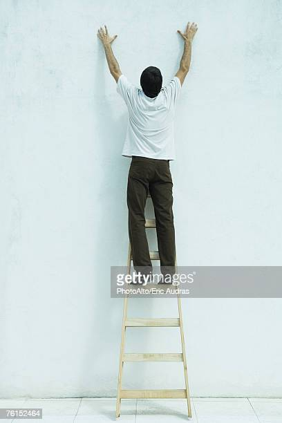 'Man standing on ladder, reaching up along wall, full length'