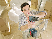 Man standing on ladder with power drill