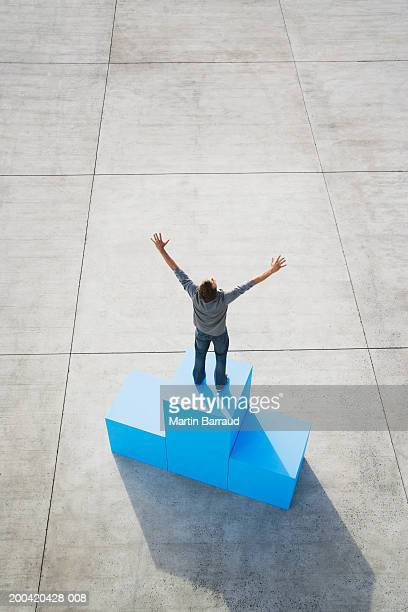 Man standing on large blue block, hands in air,  elevated view