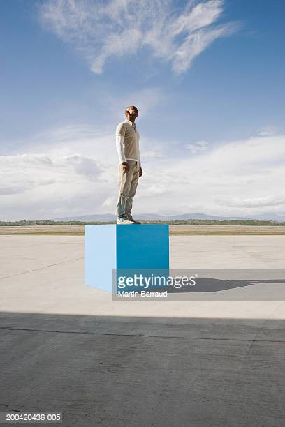 Man standing on large blue block, side view