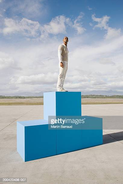 Man standing on large blue blocks, side view
