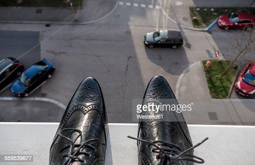 Man standing on ledge above street