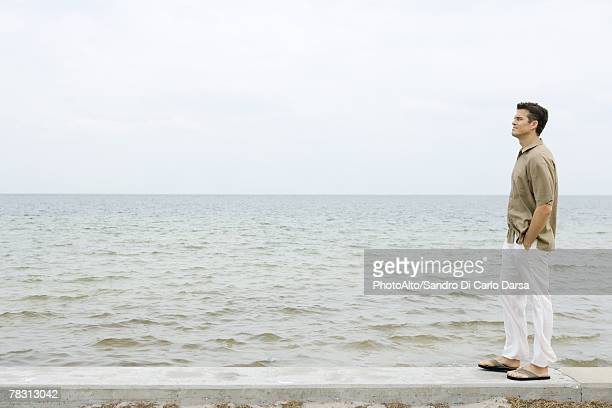 Man standing on low wall by ocean, hands in pockets, full length