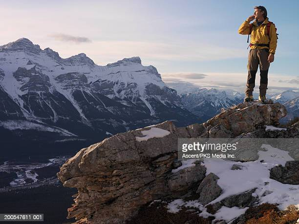 Man standing on mountain top, using mobile phone