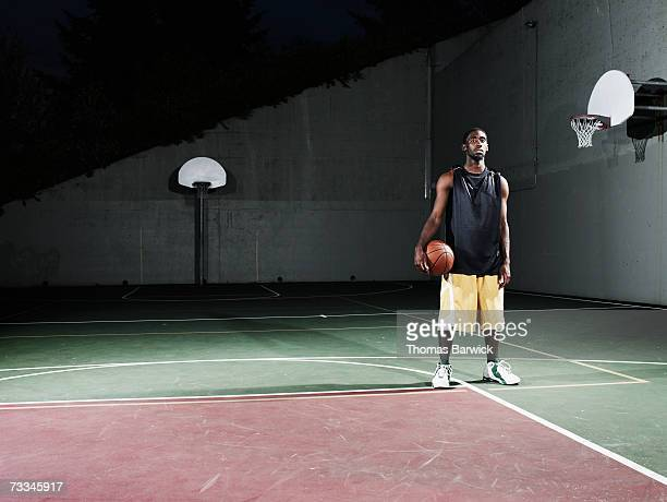 Man standing on outdoor basketball court at night