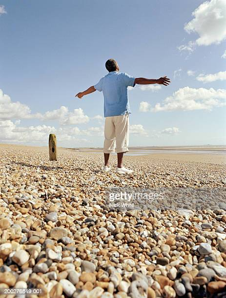 Man standing on pebble beach, arms outstretched, rear view