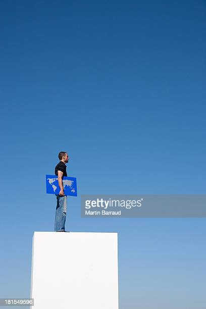 Man standing on pedestal outdoors with world map