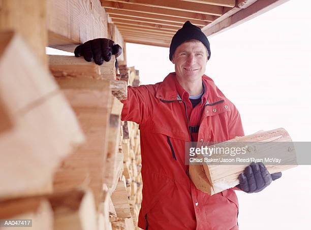 Man Standing on Porch of Log Cabin with Firewood