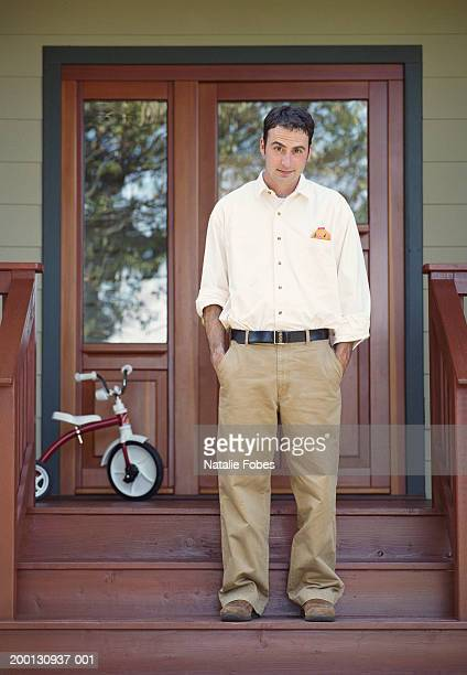 Man standing on porch steps, hands in pockets, portrait