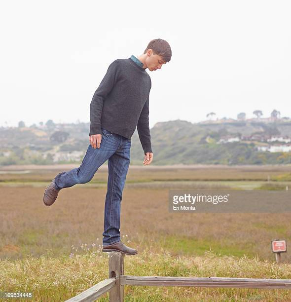 Man standing on post