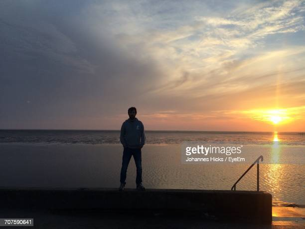 Man Standing On Retaining Wall By Sea Against Cloudy Sky During Sunset