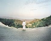Man standing on road in barren landscape