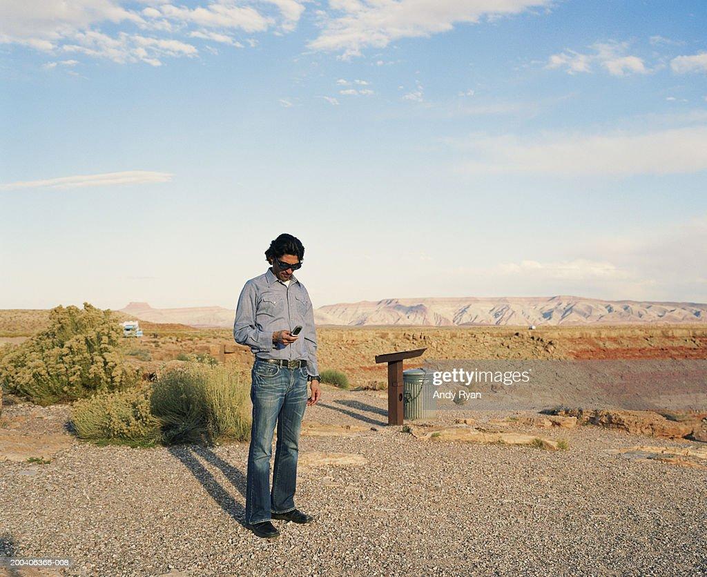 Man standing on road in desert landscape using mobile phone : Stock Photo