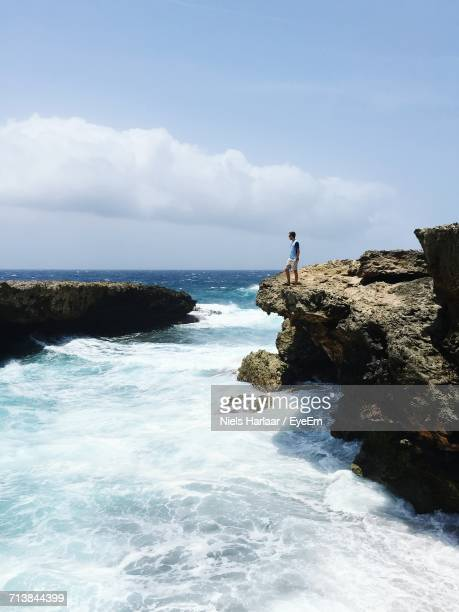 Man Standing On Rock Formation By Sea Against Cloudy Sky