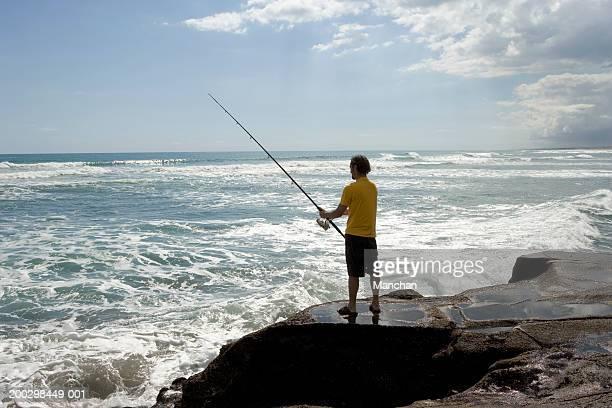 Man standing on rocks fishing in sea, rear view