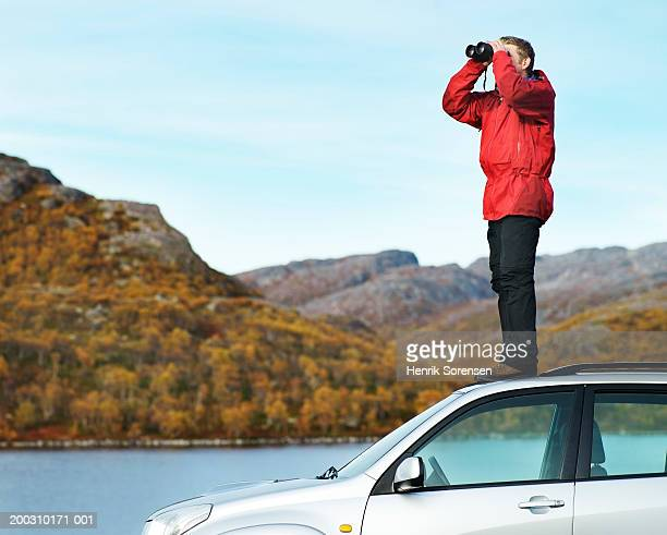 Man standing on roof of car, looking through binoculars