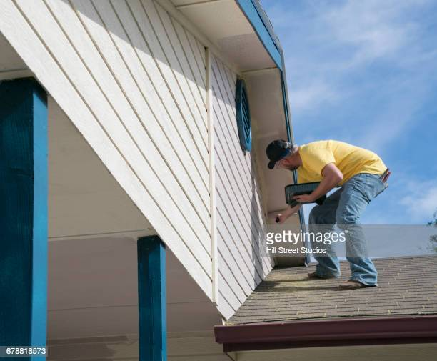 Man standing on roof painting house