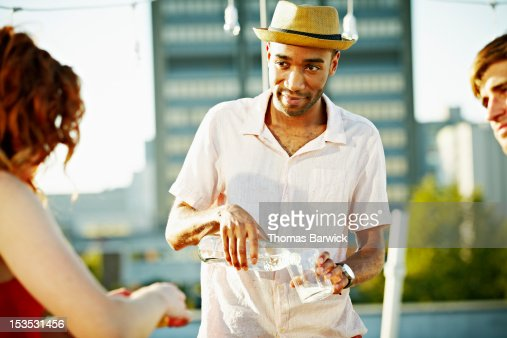 Man standing on rooftop deck with friends smiling : Stock Photo